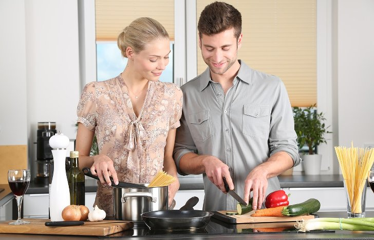 Mann und Frau stehen vor dem Herd und Kochen gemeinsam