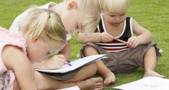 3 kleine Kinder sitzen im Garten und malen
